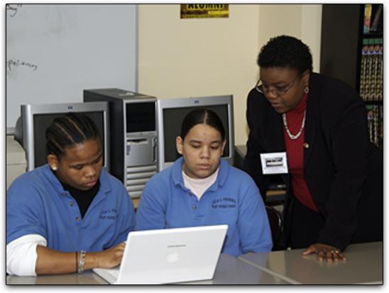 Professor orientando alunos em sala de aula usando Macs