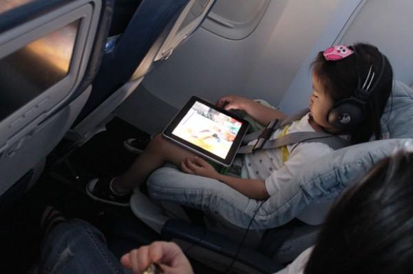 Garotinha usando iPad em avião