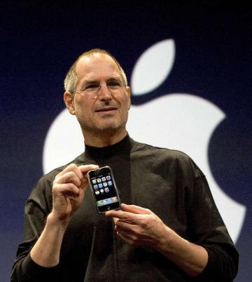 Steve Jobs com iPhone e logo da Apple ao fundo