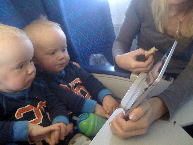 Crianças entretidas com um iPad em um avião