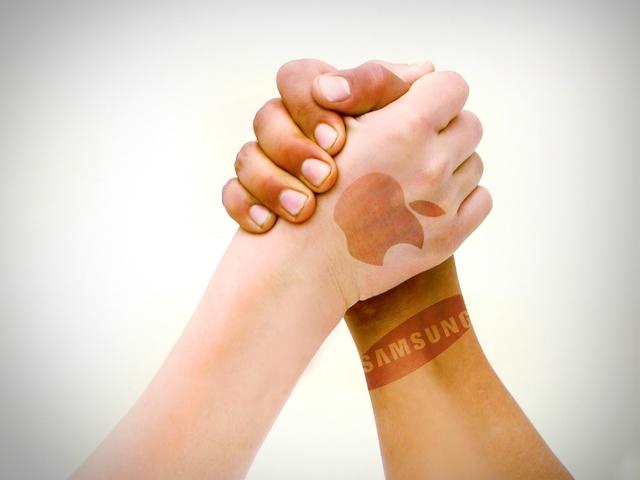 Mãos marcadas com os logos de Apple e Samsung