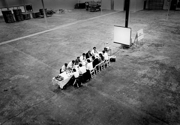 Executivos numa mesa dentro de um galpão - Foto de Doug Menuez