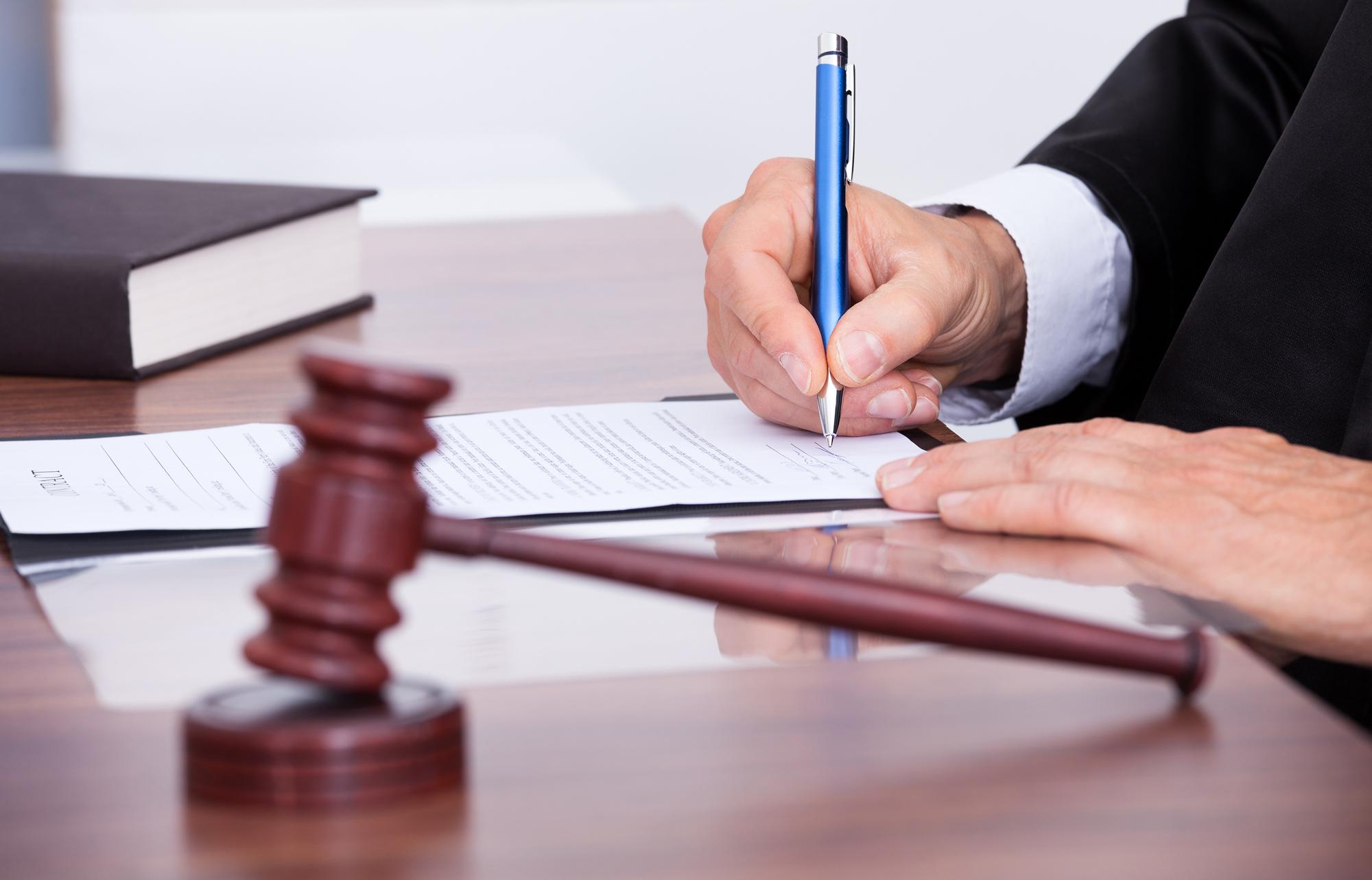 Homem assinando papel em tribunal