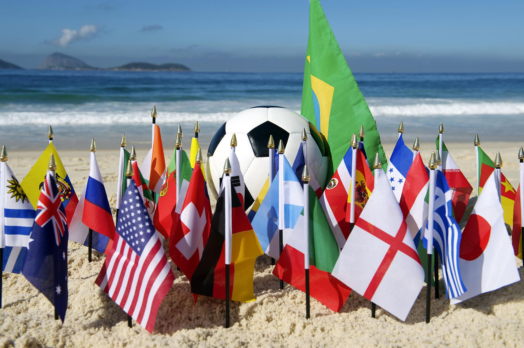 Bola de futebol na praia com bandeiras de países