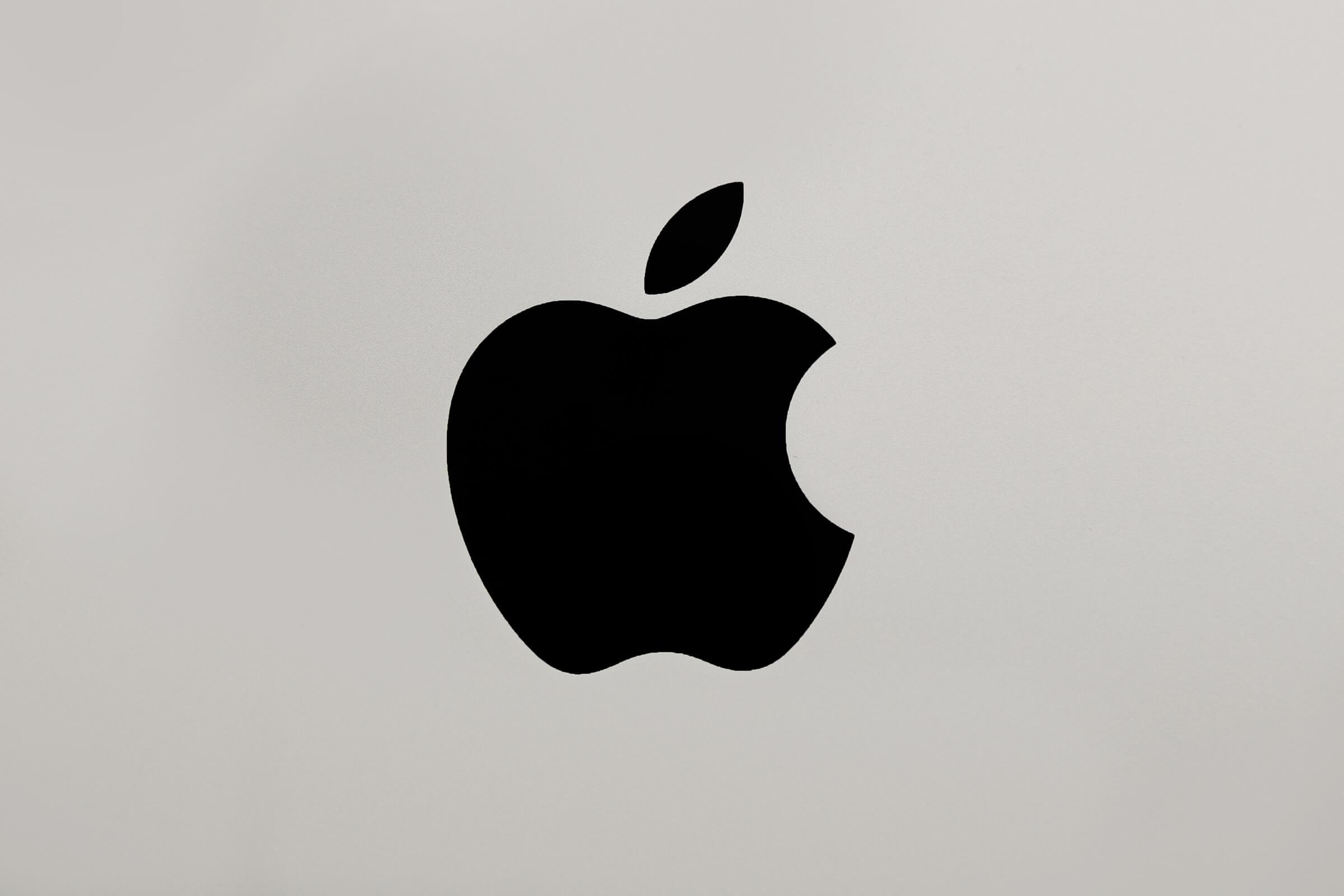 Logo da Apple preto sobre uma superfície de alumínio escovado