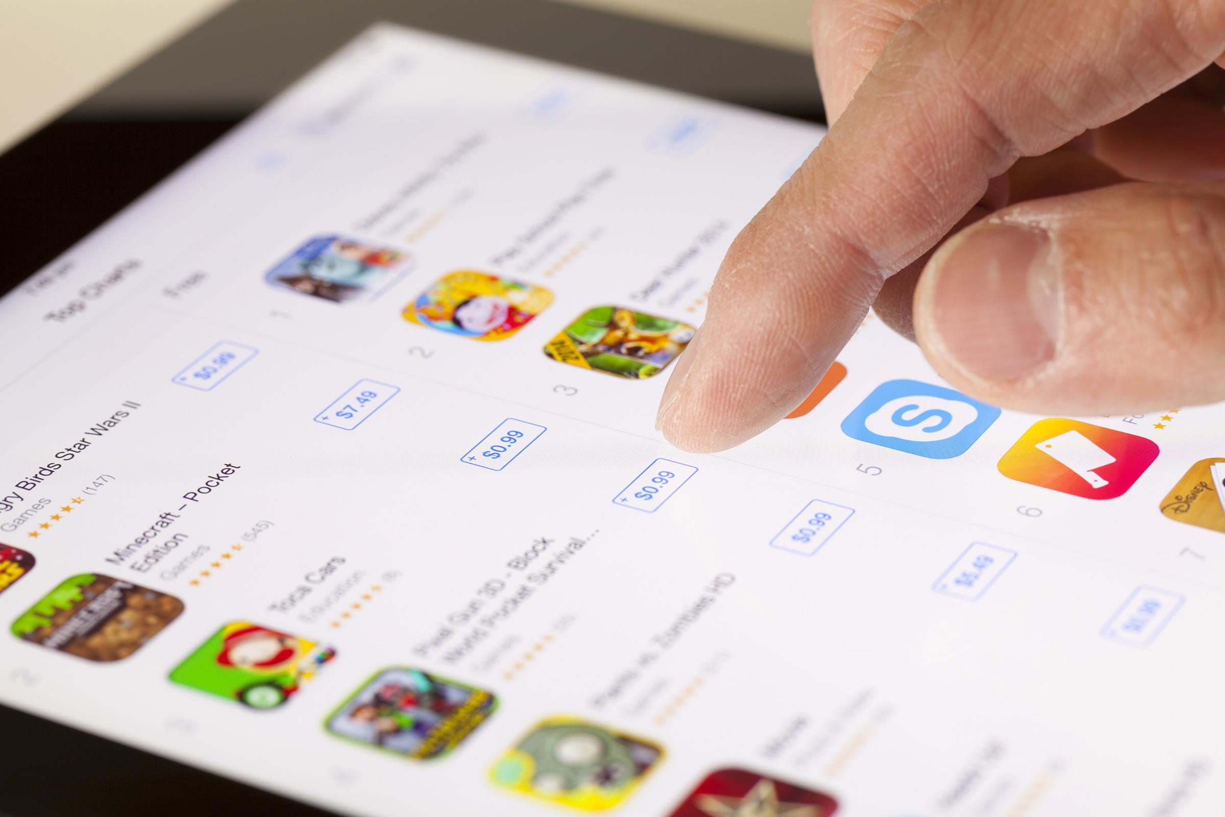Mão tocando na App Store num iPad