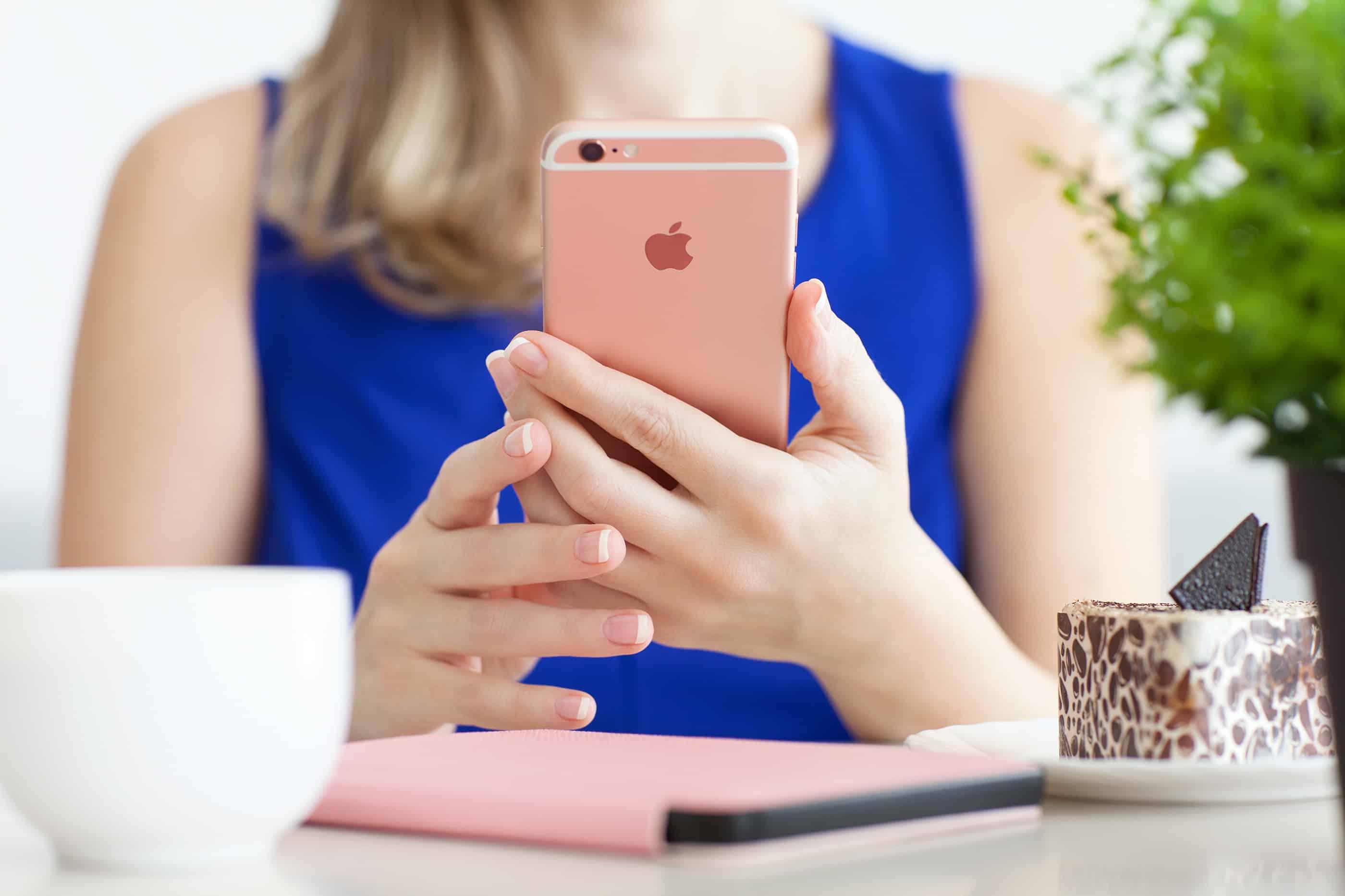 Mulher lendo em iPhone 6s ouro rosé