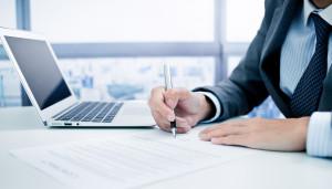 Assinando contrato de emprego com MacBook Air ao lado