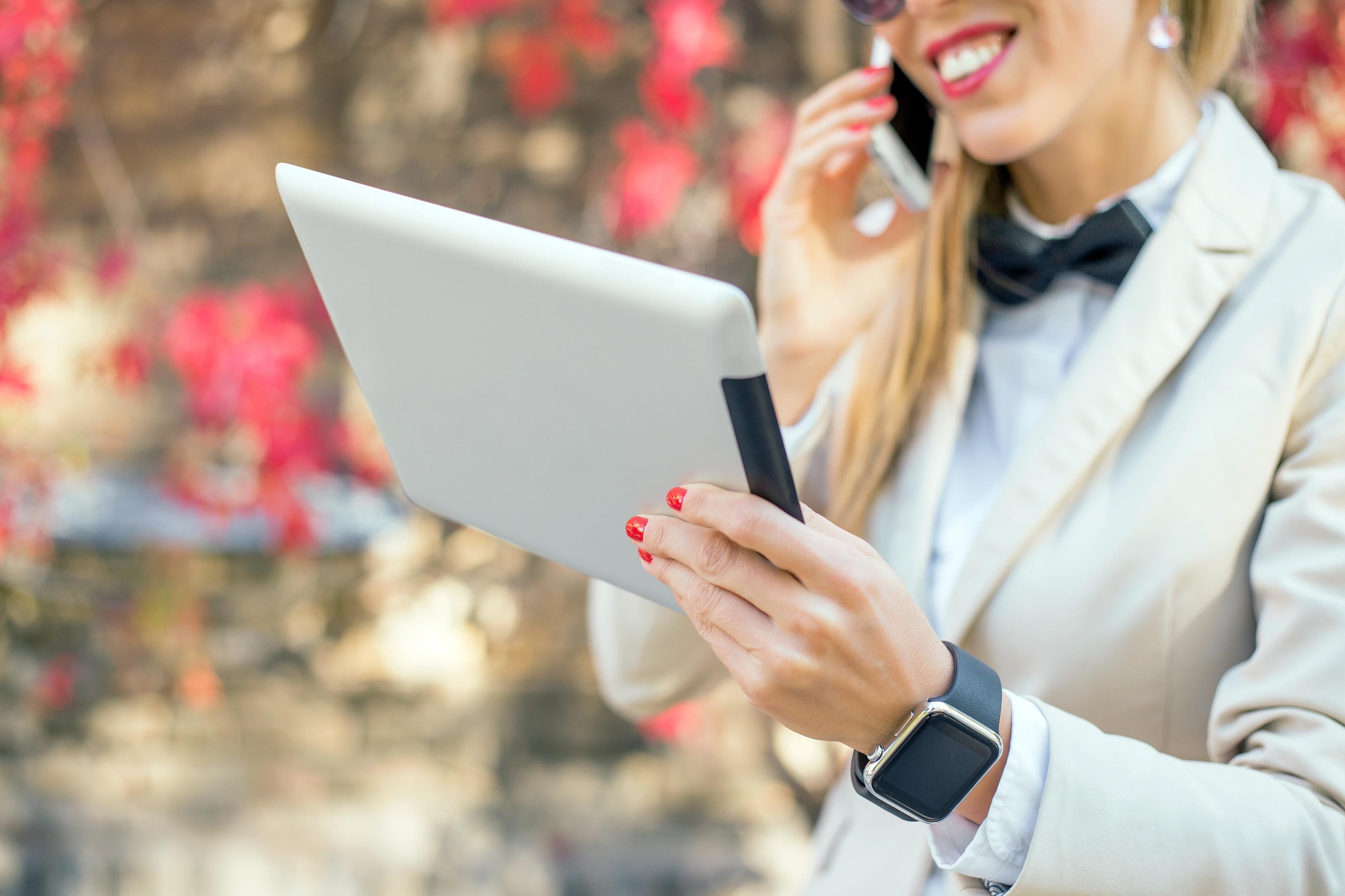 Mulher usando Apple Watch e segurando iPad
