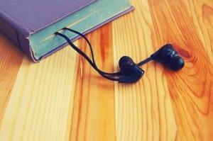 Imagem de um livro com fones de ouvido dentro