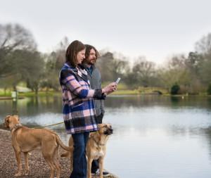 Casal em pé com um cachorro perto de um lago (CareKit)