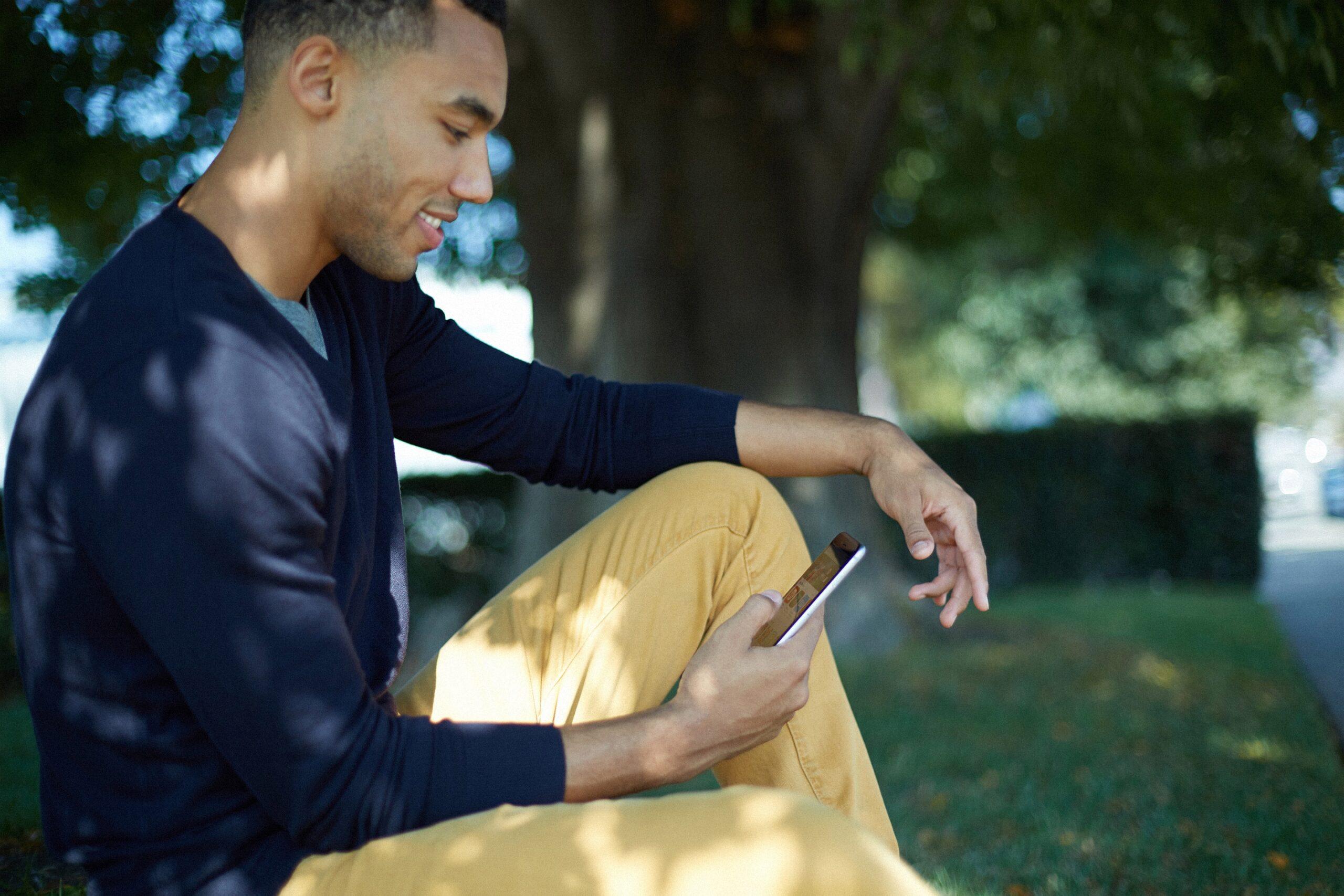 Homem usando iPhone num parque