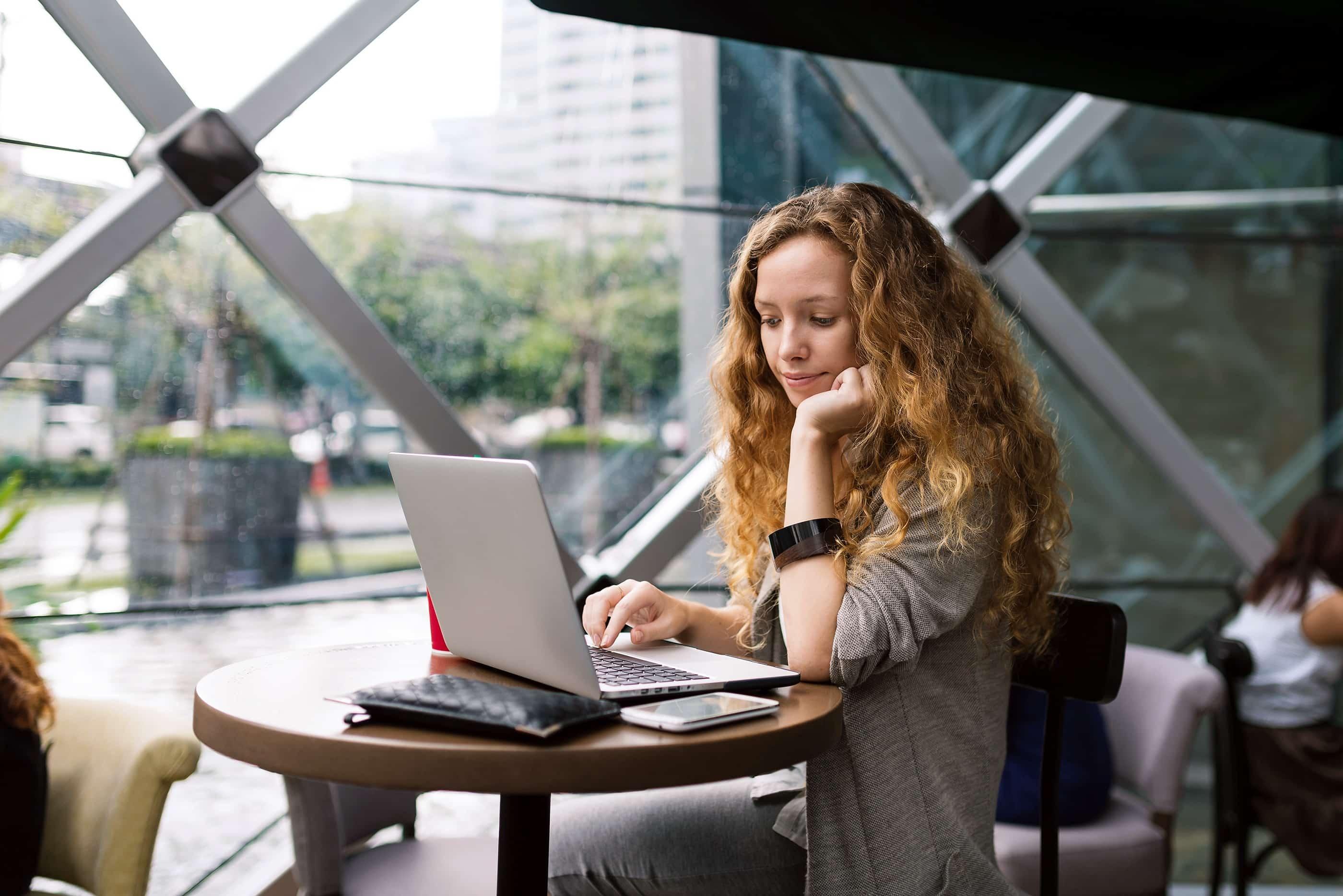 Mulher usando MacBook numa cafeteria