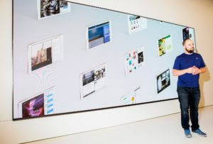 Empregado da Apple com um painel cheio de iPads ao fundo