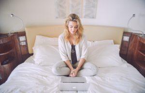 Mulher sentada na cama com um MacBook Pro