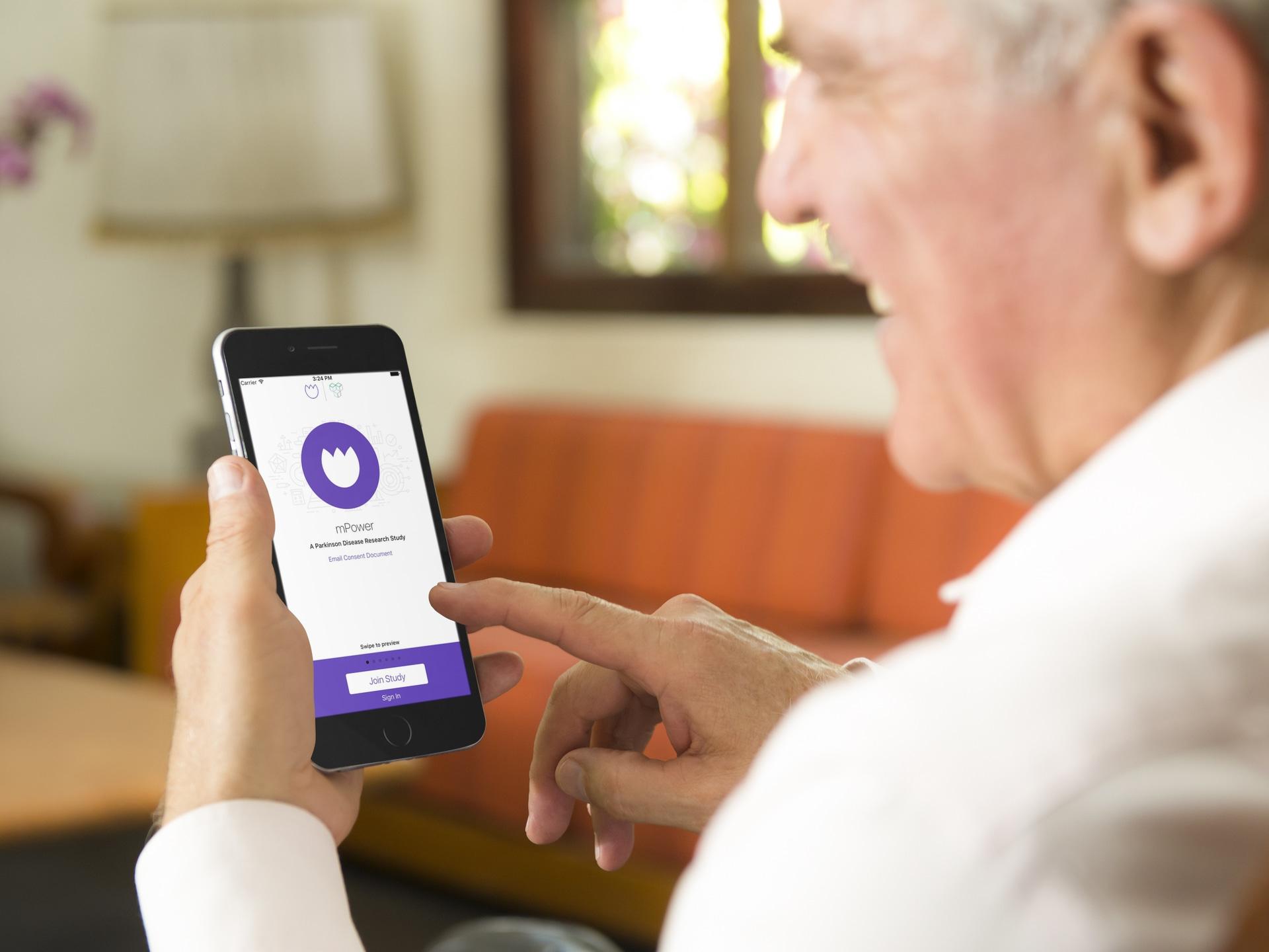 App mPower do Mal de Parkinson sendo usado por idoso num iPhone