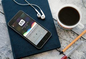Podcast #211 (MacMagazine no Ar) num iPhone sobre mesa com café e fones de ouvido