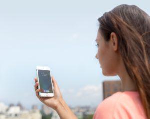 Mulher usando a Siri num iPhone ao ar livre