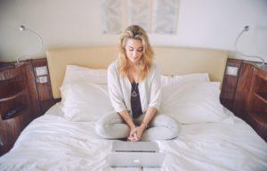 Mulher sentada na cama com um Mac