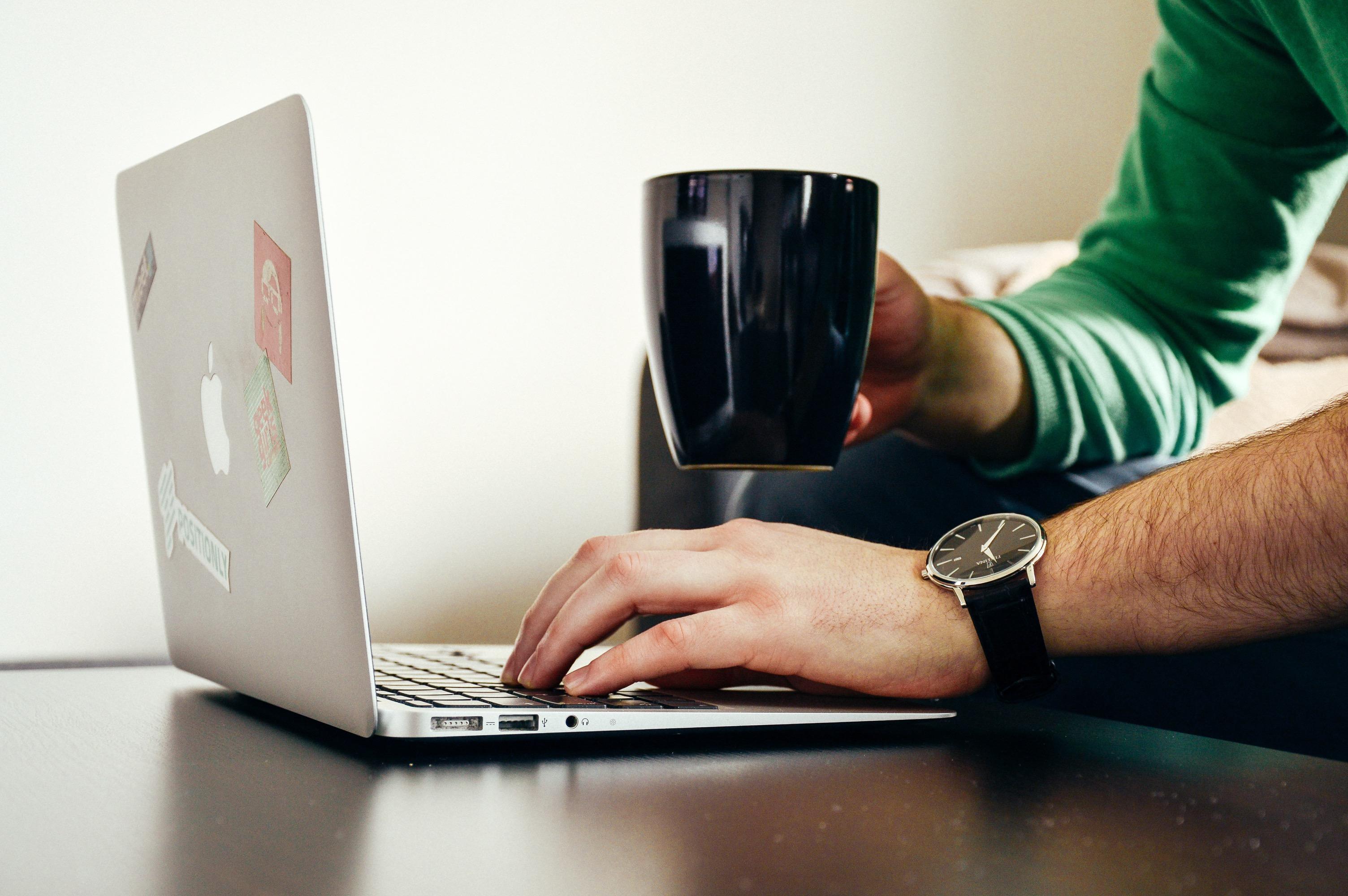 Homem usando um MacBook Air com uma xícara de café