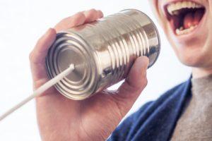 Pessoa falando num telefone sem fio de lata