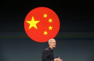 Tim Cook em evento da Apple com a bandeira da China ao fundo