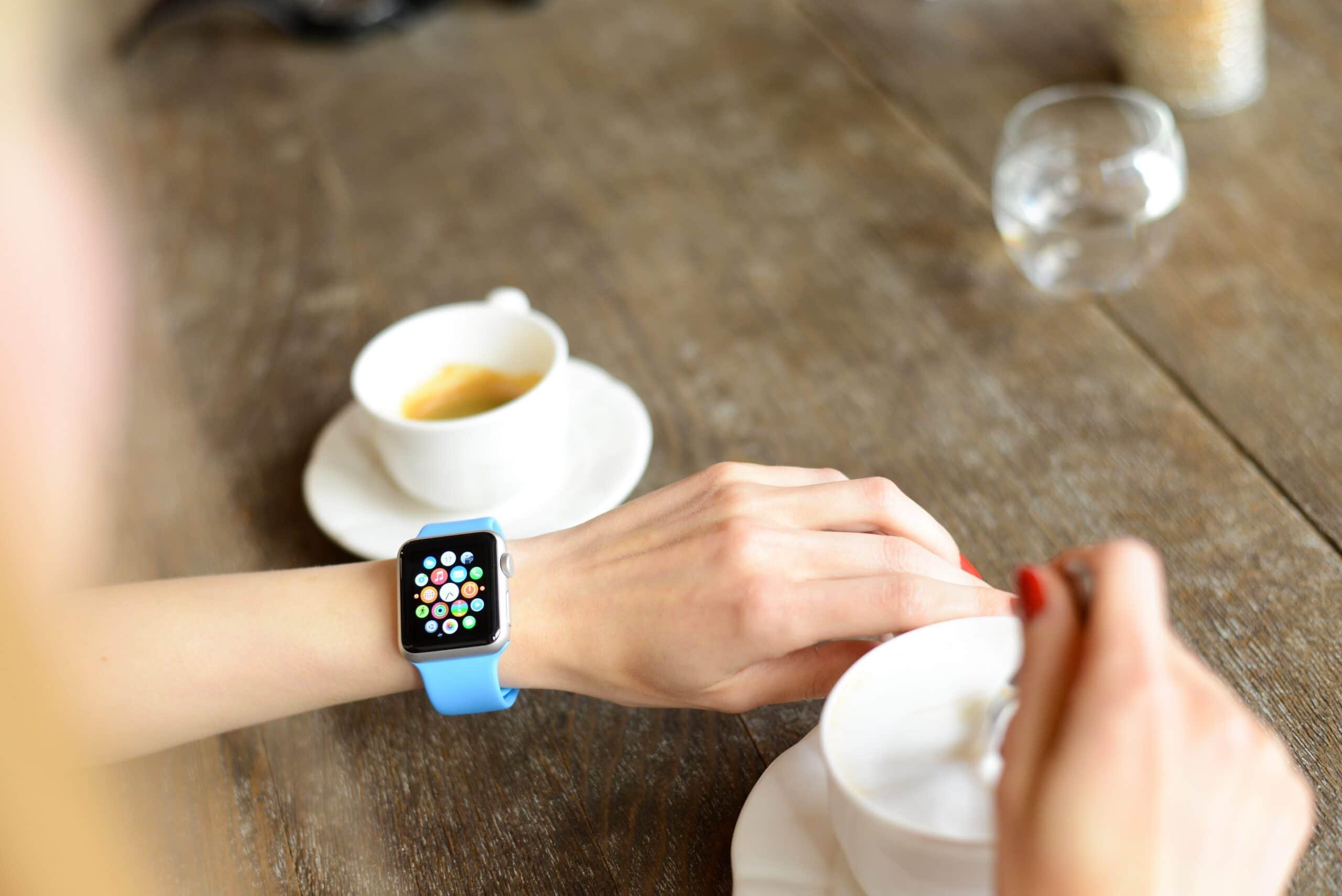Apple Watch no braço de mulher com café ao lado