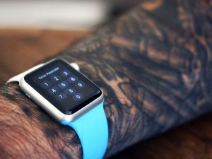 Braço com tatuagem usando o Apple Watch