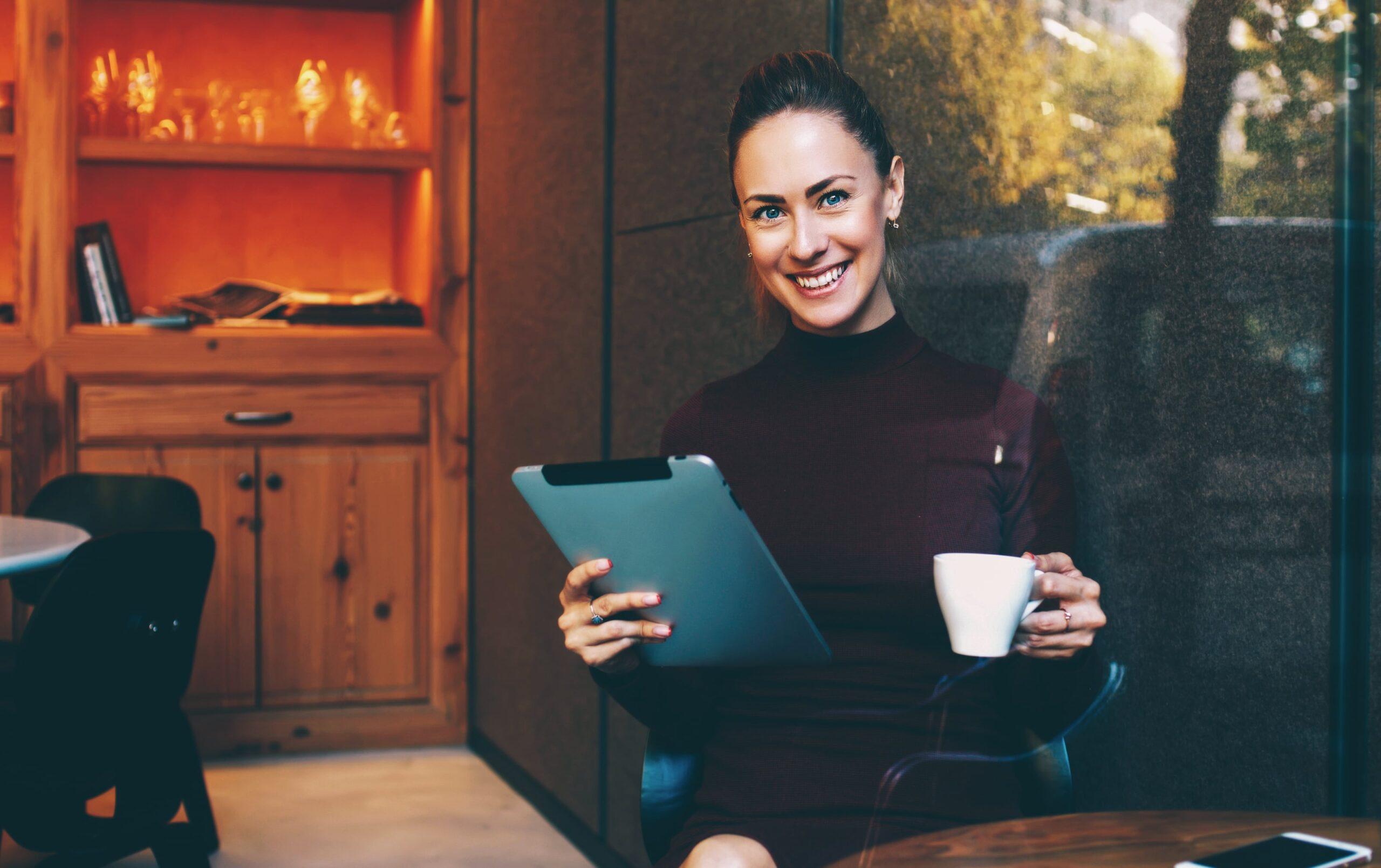 Mulher lendo em iPad e tomando café