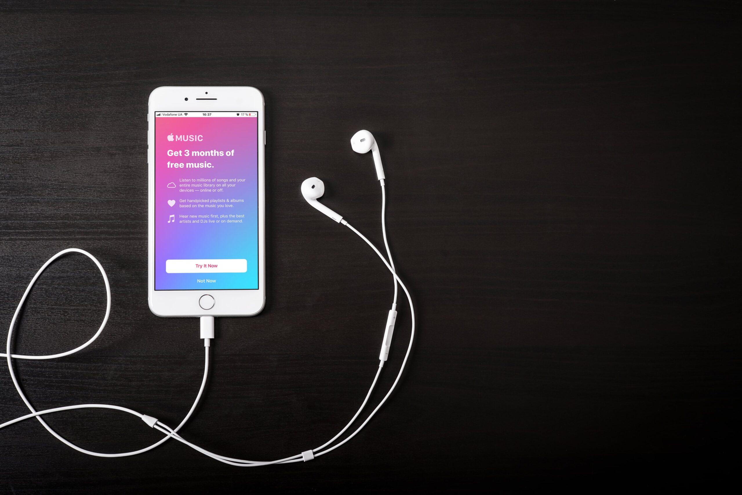 iPhone com Apple Music e EarPods com fio numa mesa