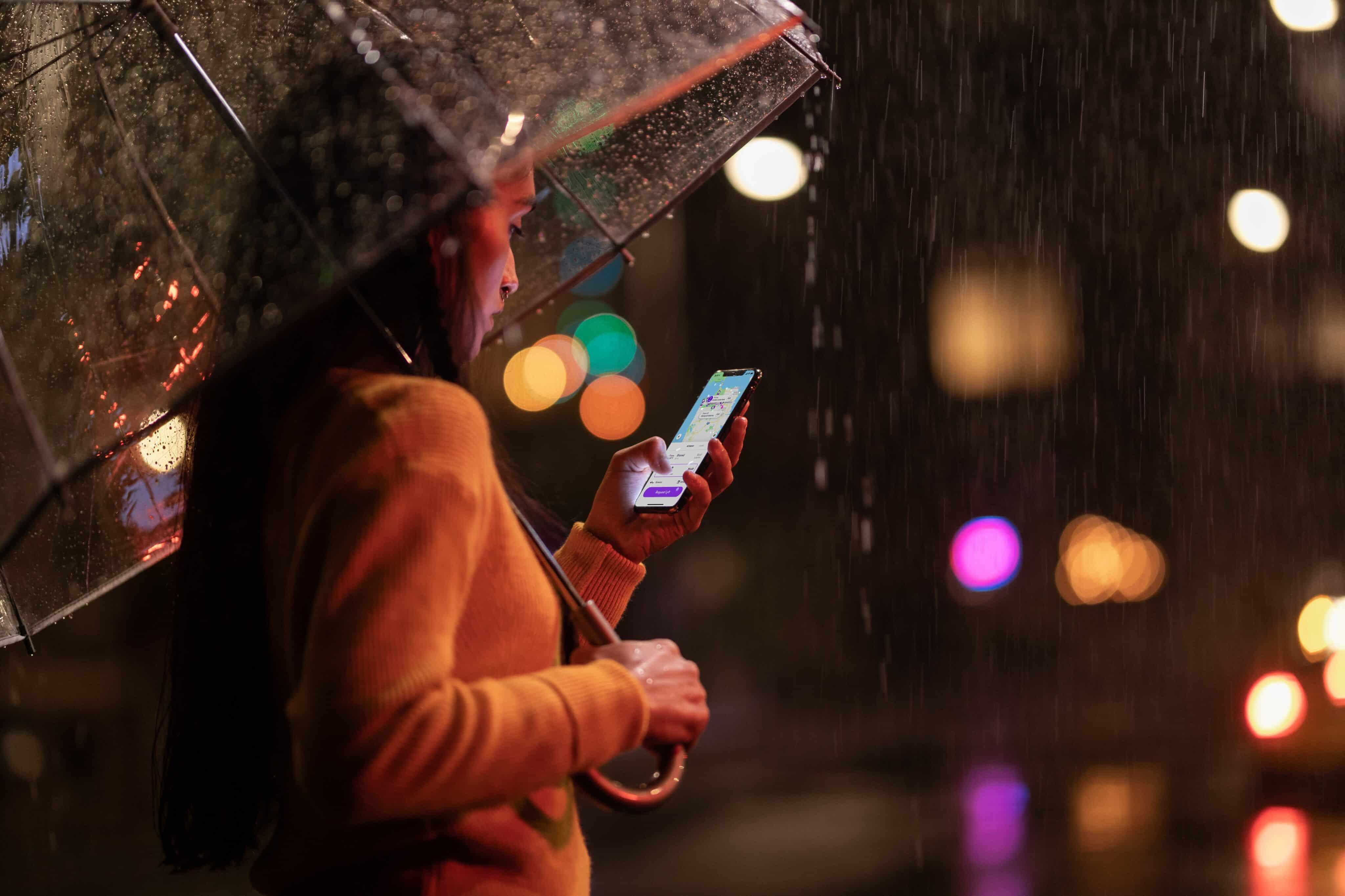 Pessoa na chuva usando um iPhone Xs