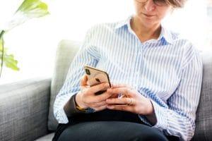 Mulher usando um iPhone XS dourado