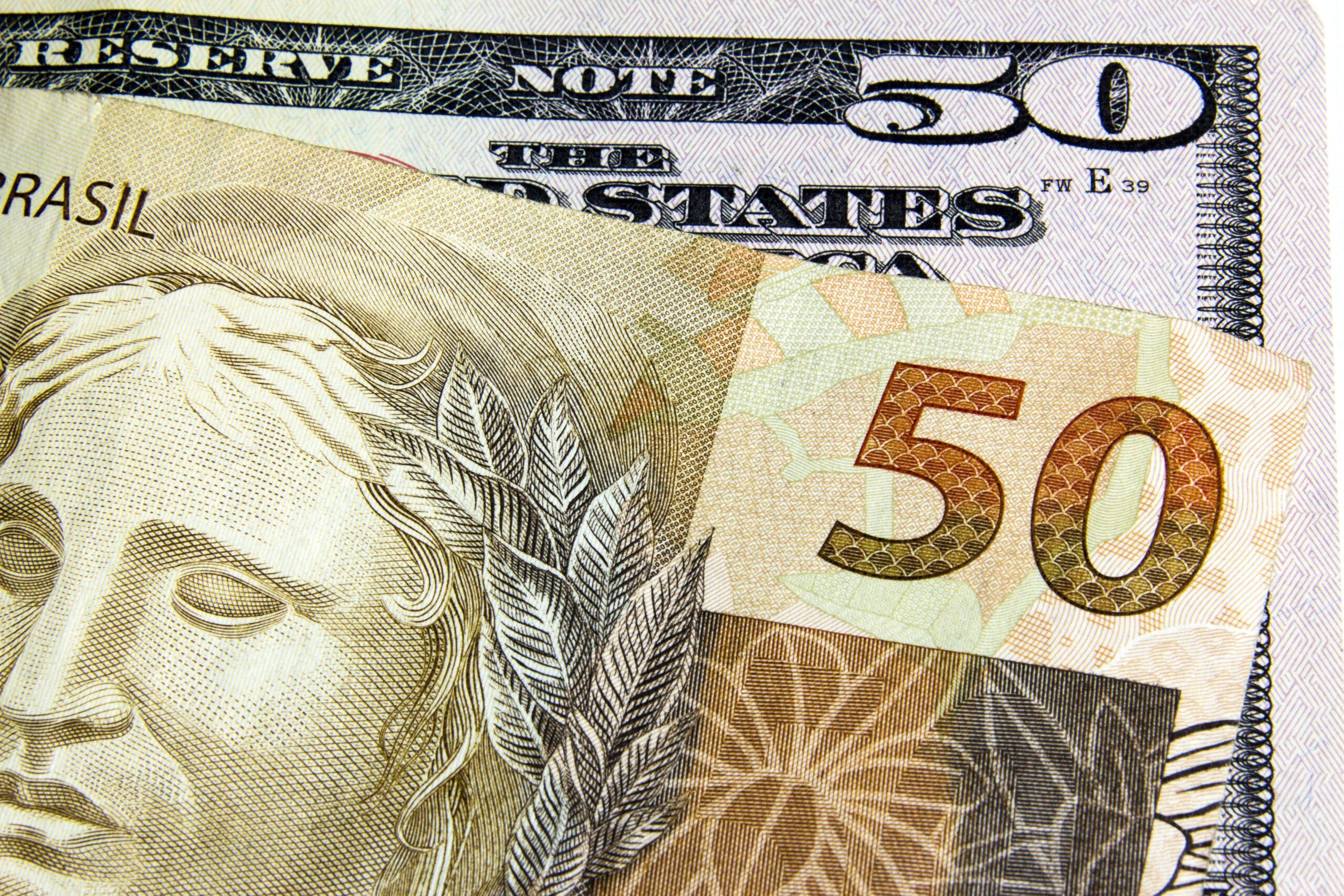 Notas de 50 dólares e real - dinheiro