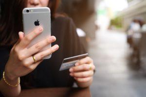 Mulher com um iPhone 6 e um cartão de crédito