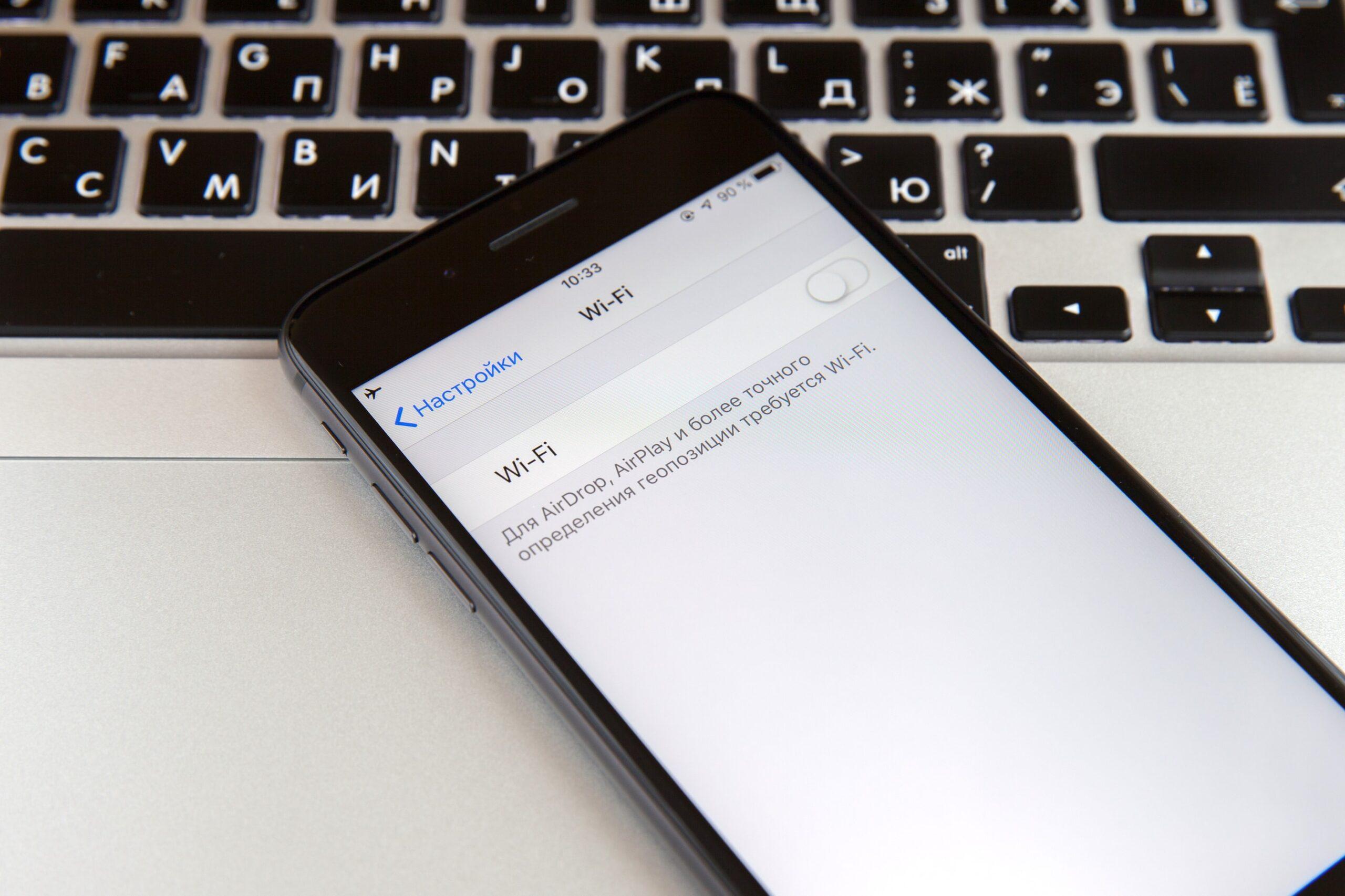 iPhone com Ajustes abertos no Wi-Fi em cima de um MacBook Pro