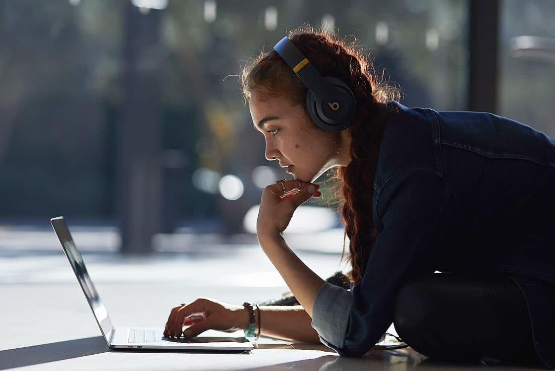 Menina/mulher usando MacBook com fones da Beats