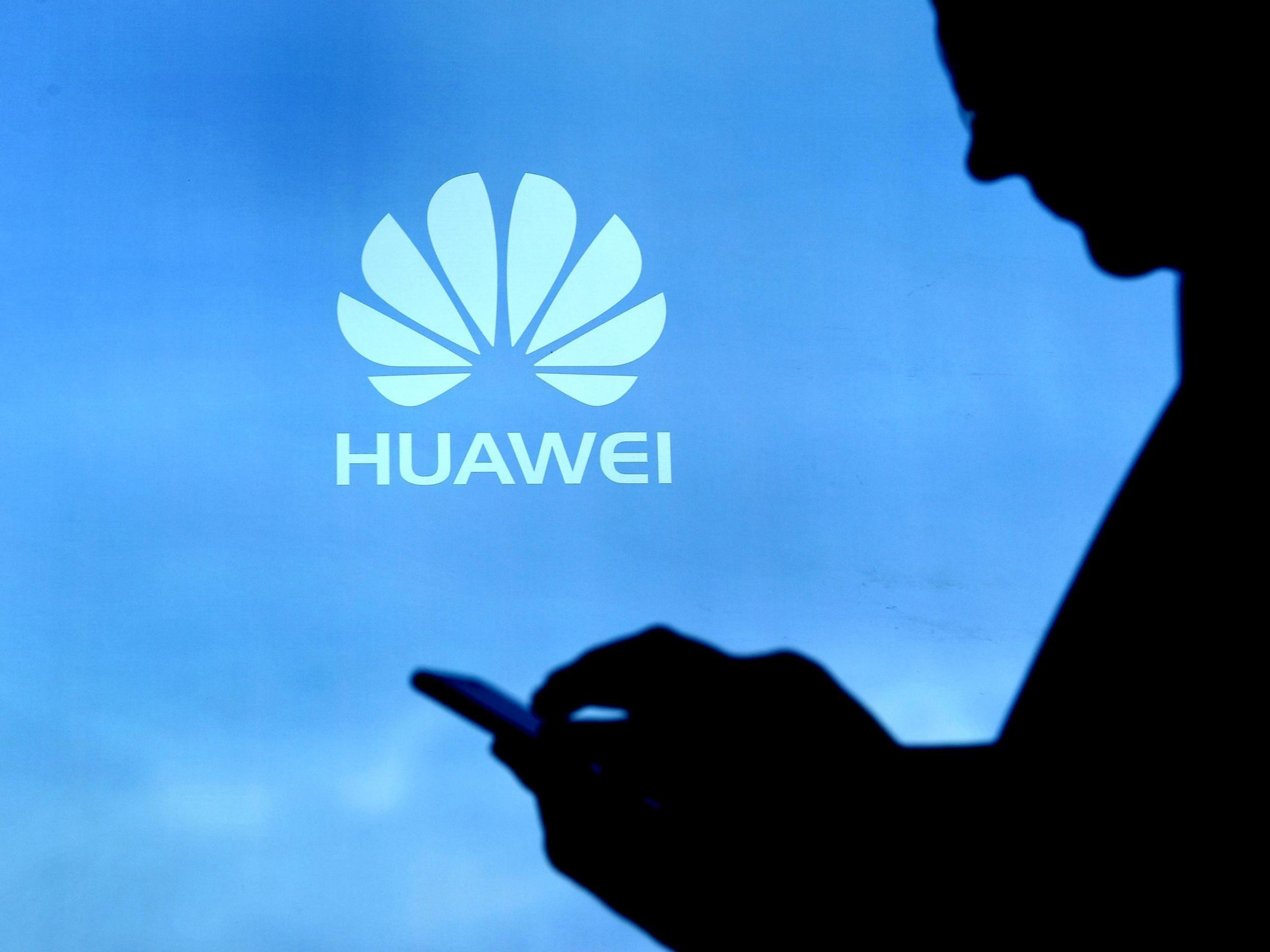 Homem usado celular e o logo da Huawei ao fundo