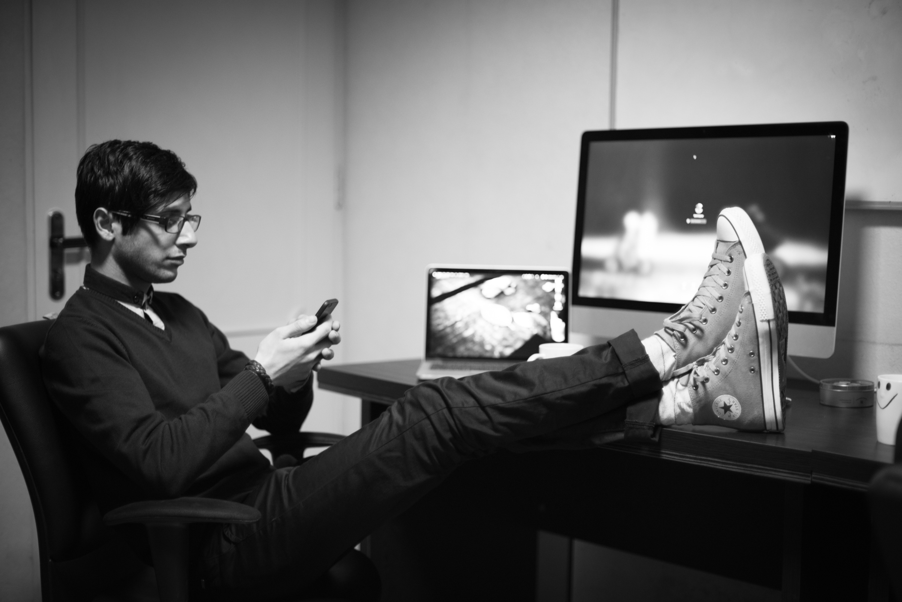 Homem usando iPhone com iMac e MacBook Pro ao fundo
