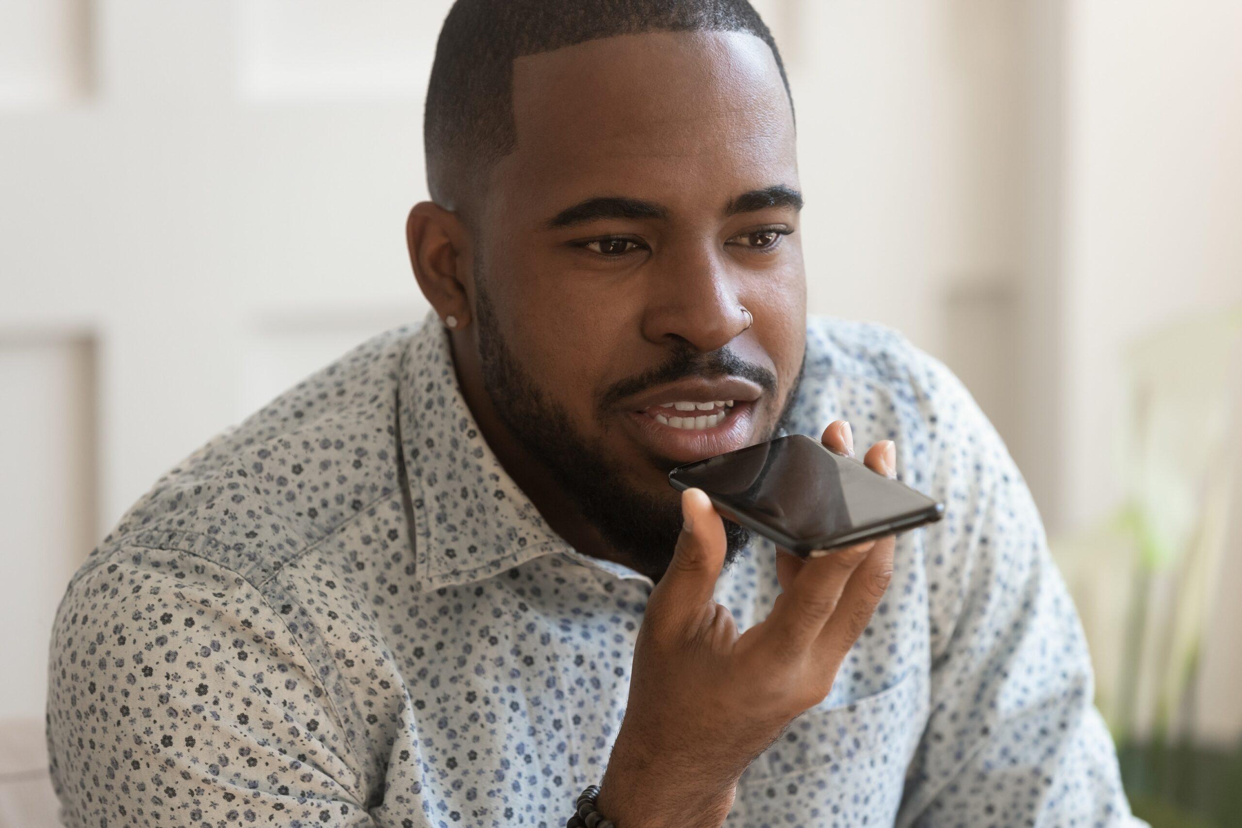 Homem falando com o iPhone, segurando aparelho com uma mão