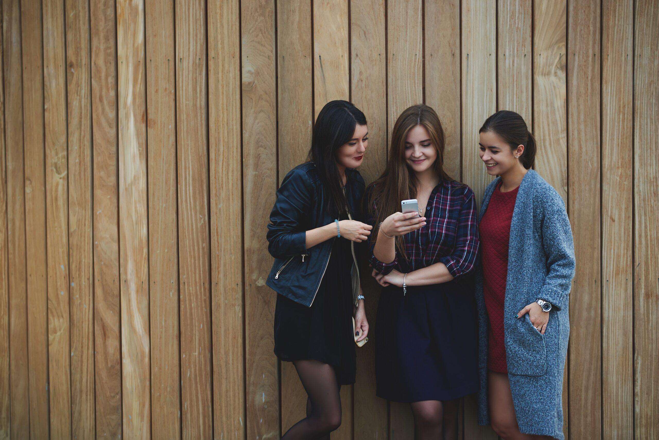 Três mulheres olhando algo em um iPhone