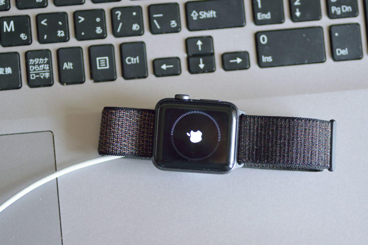 Apple Watch atualizando conectado à energia em cima de MacBook Pro