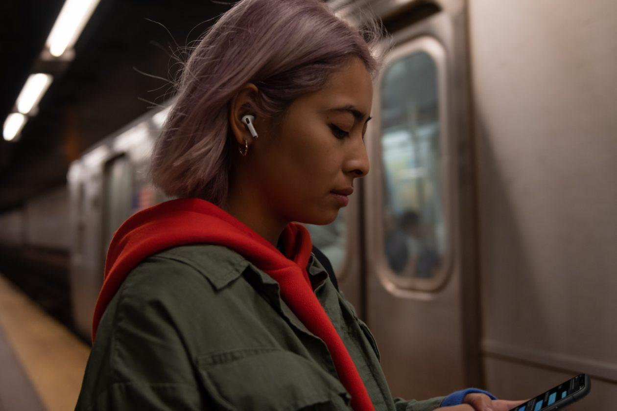Mulher usando os AirPods Pro no metrô