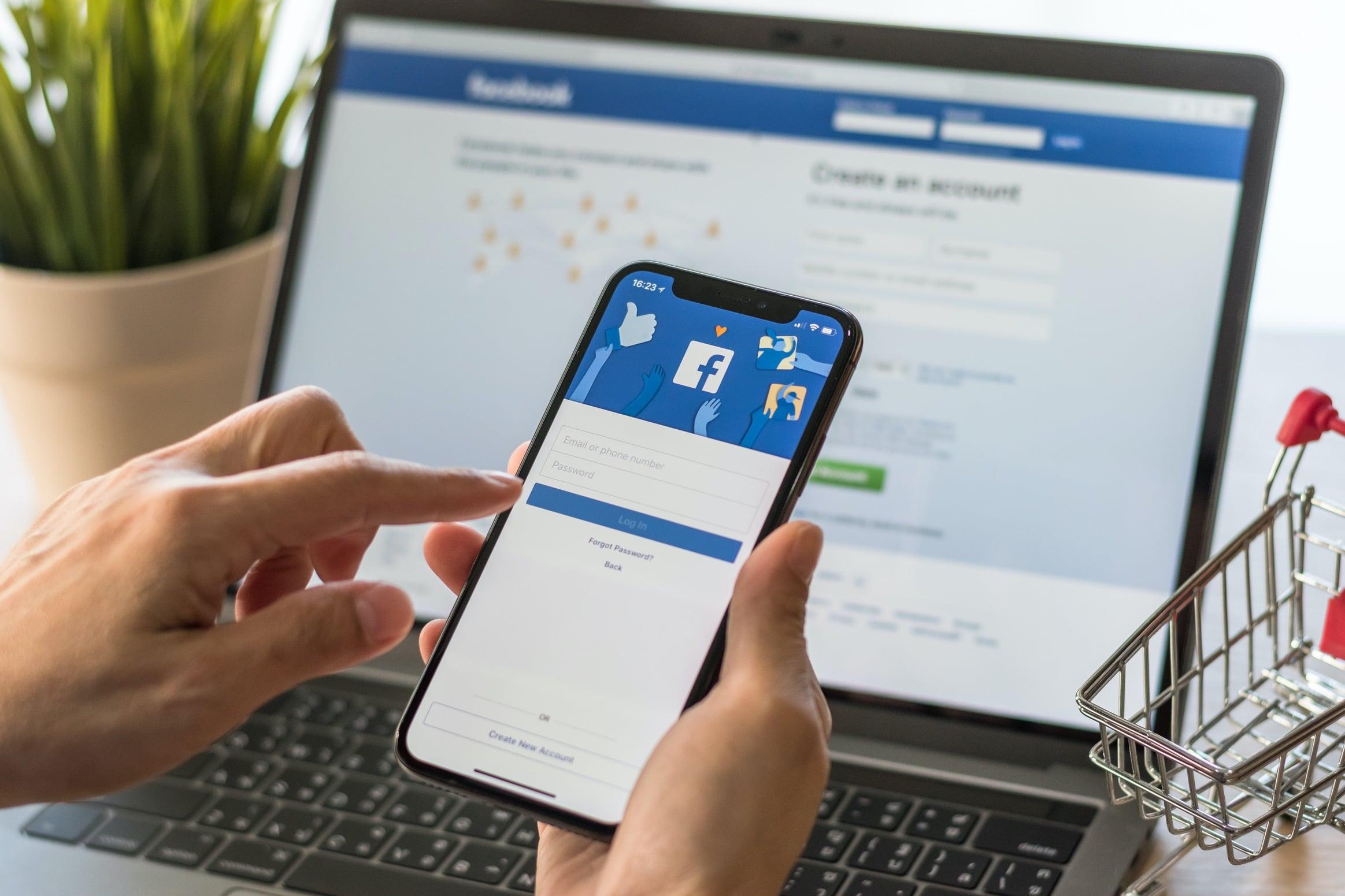 Facebook em iPhone com computador no fundo