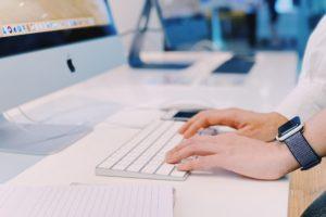 Pessoa digitando em Magic Keyboard conectado a um iMac