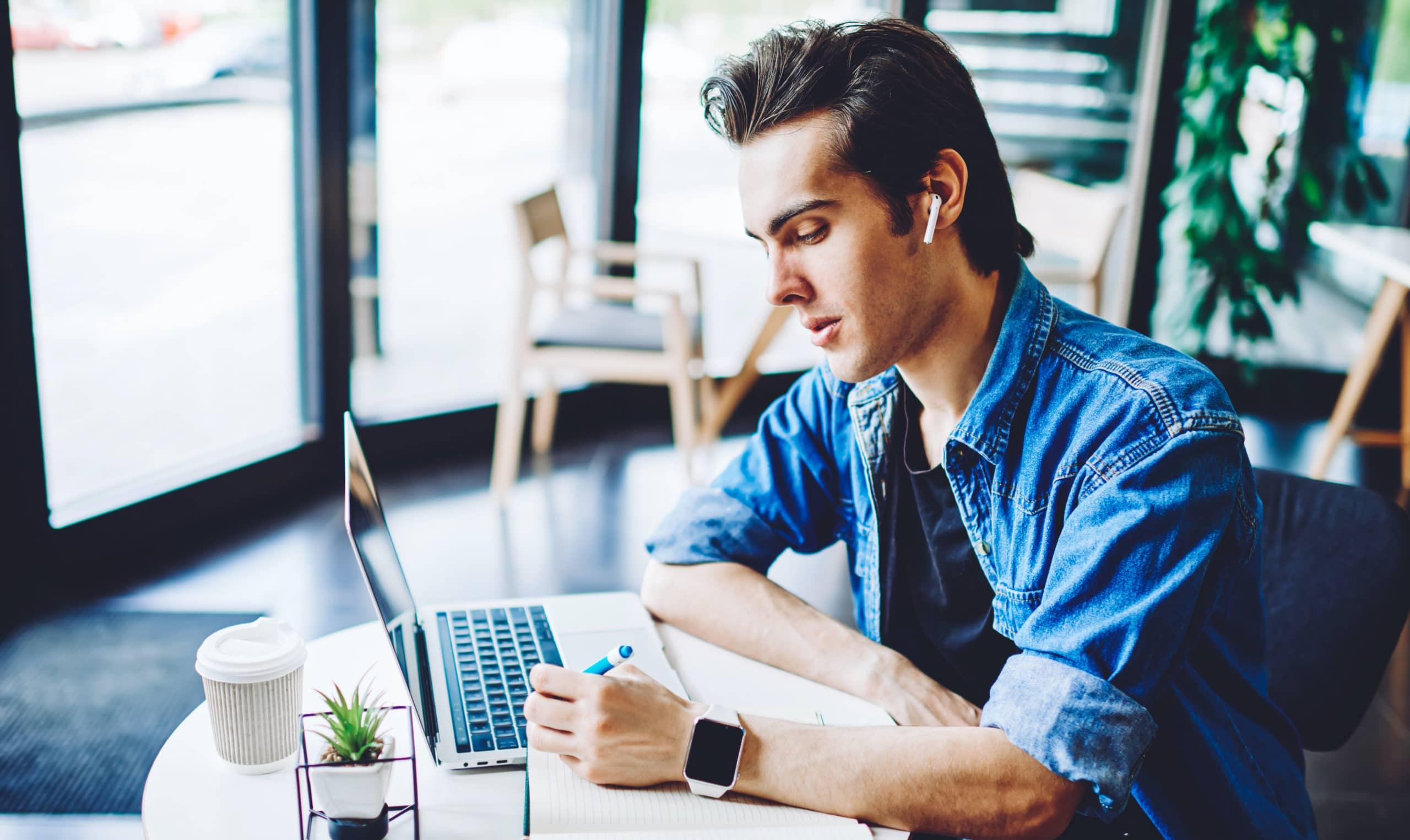 Homem usando AirPods e Apple Watch trabalhando no computador