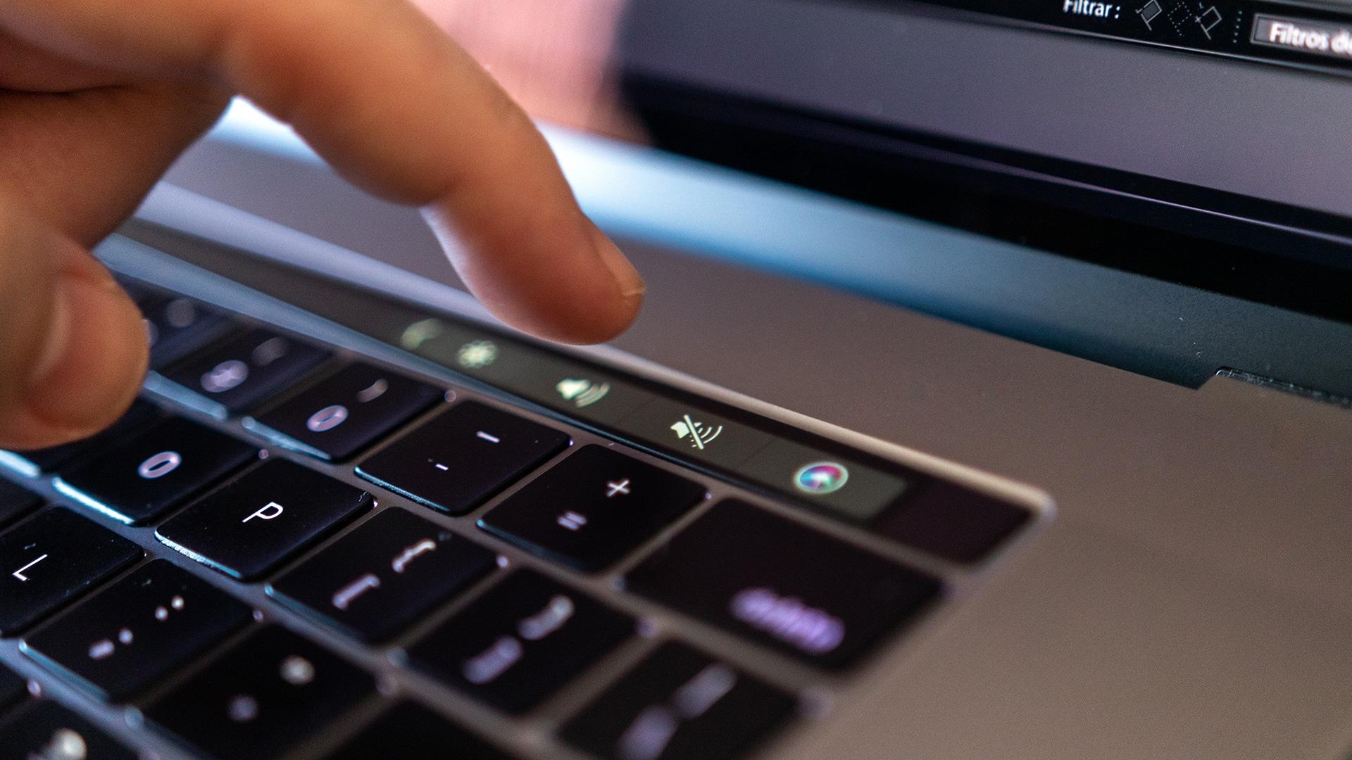 Dedo mexendo na Touch Bar de MacBook Pro