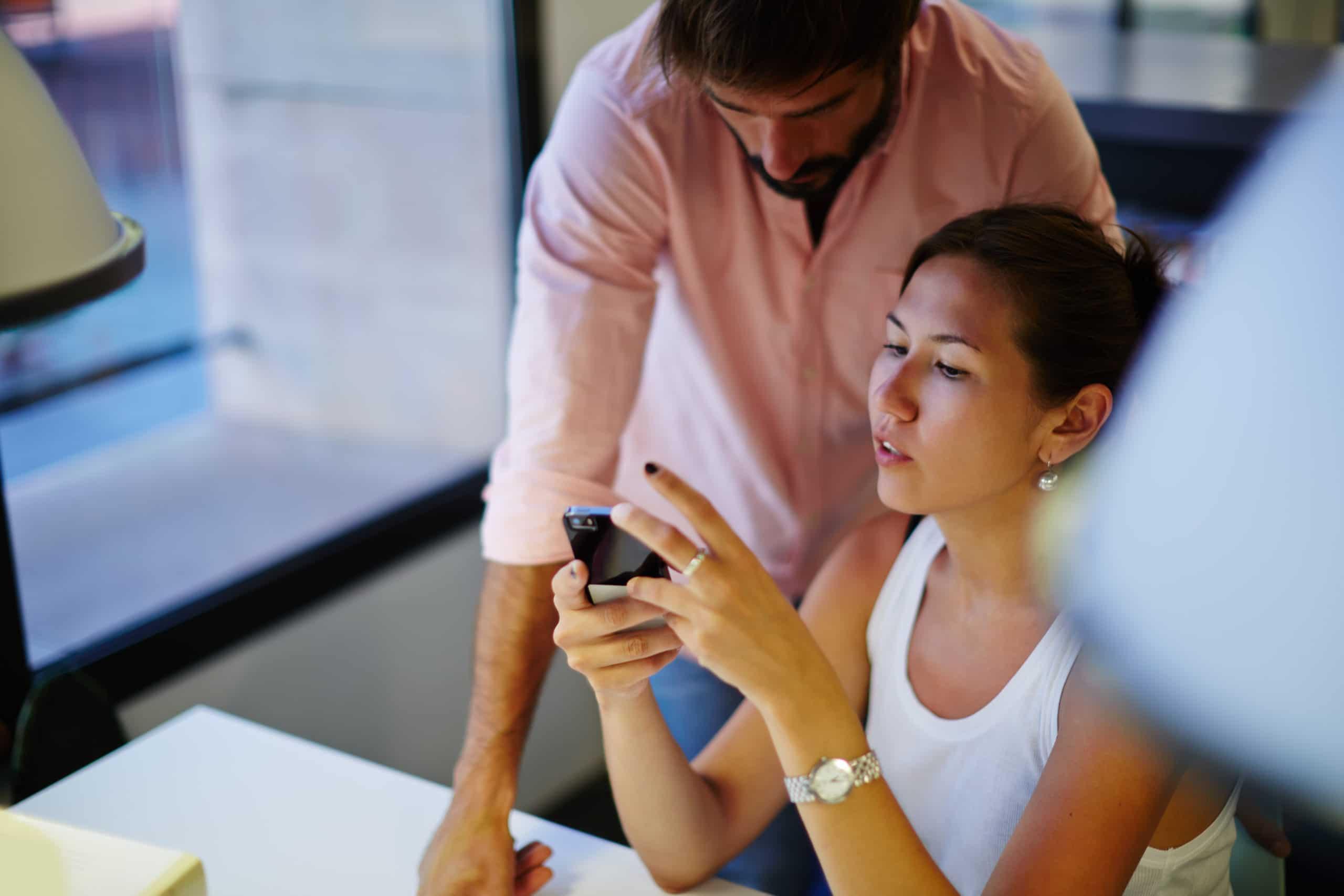 Duas pessoas conversando e olhando para a tela do iPhone