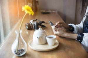 Leitura em iPhone com café e flor