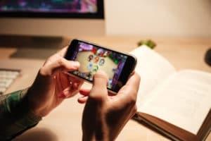 Jogando em iPhone com livro ao fundo