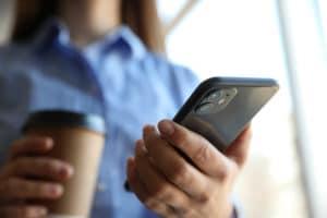 Mulher com iPhone 11 Pro e café na mão